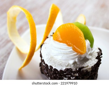 macro cake with cream, chocolate  crumb and slices of orange and lime on white plate on blurred background
