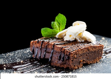 Macro close up of appetizing chocolate brownie with dark chocolate dressing and vanilla ice cream against black background.