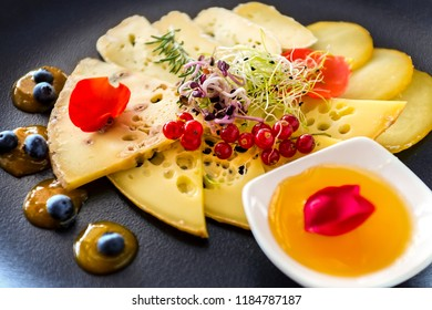 Macro close up of appetizing matured cheese slices with fruits and marmalade on black plate.