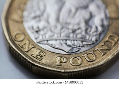 Macro close up of a british one pound coin showing the writing, on a white background