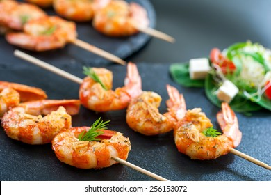 Macro close up of catering shrimp brochettes grilled with herbs. Out of focus salad in background.