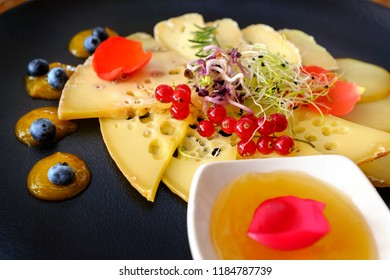 Macro close up of cheese platter with variety of matured cheeses  and fruits on black plate.