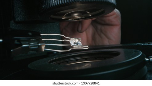 Macro close up of experienced goldsmith controlling a quality of diamond stone, selected for making jewels in workshop.Concept of jewelry,luxury,goldsmith, diamonds, brilliance.