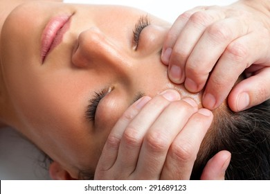 Macro close up face shot of young woman receiving massage. Therapist hand doing manipulative treatment on forehead.