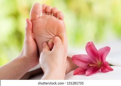 Macro close up of female hands massaging girls foot.