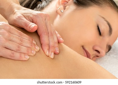 Macro close up of hands doing healing shoulder massage on woman in spa.