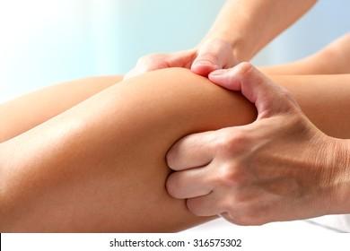 Macro close up of hands doing manipulative healing massage on female calf muscle.