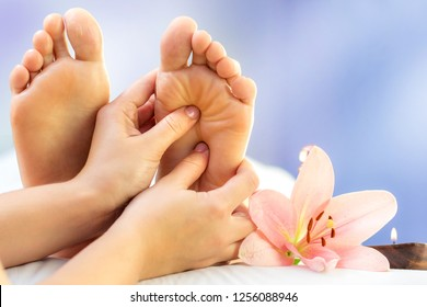 Macro close up of hands massaging female foot. Feet next to flower and candle against colourful background.