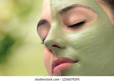 Macro close up head shot of attractive woman with green algae facial mask in spa.