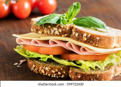 Macro close up healthy ham, cheese and tomato wholewheat sandwich on wooden table.