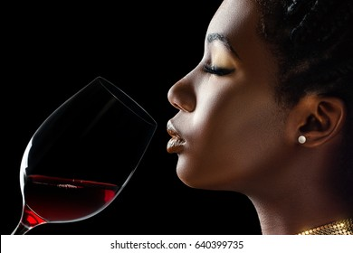 Macro close up low key portrait of sensual african woman smelling red wine.Side view of girl with red wine glass next to face against black background.