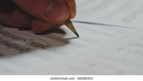 Macro close up of musician or composer hand writes a song or a musical work, writing notes with pencil on the pentagram. Concept: conservatory, music, composer, notes, art, life