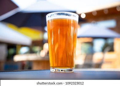 Macro close up on a pint glass of India Pale Ale beer, at an outdoor patio of a craft brewery, with space for text on the right
