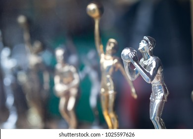 Macro close up on a shelf of small basketball trophy figurines, with a silver plated player shooting, for an athletic sports award