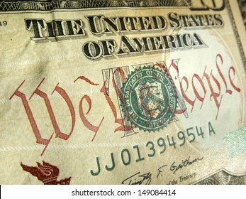 """A macro close up photo emphasizing the inscription """"We The People"""" printed on the back of a United States ten dollar bill with selective focus on the words 'We The People'."""