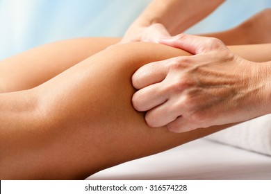 Macro close up of Physiotherapist hands massaging female calf muscle.