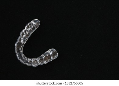 Macro close up of a plastic teethguard to stop wear due to teeth grinding at night isolated against black background.