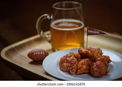 macro close up of plate of boneless hot wings and glass mug of beer for big football game