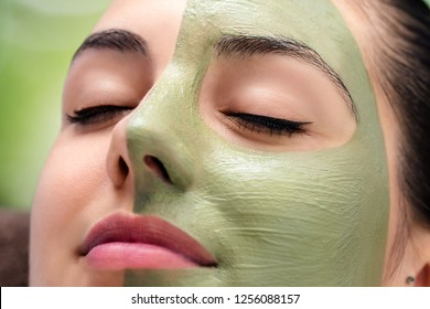 Macro close up portrait of woman having facial cosmetic green algae treatment in spa.