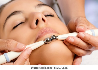 Macro close up portrait of woman having cosmetic galvanic beauty treatment in spa.Therapist applying low frequency current with electrodes on face.