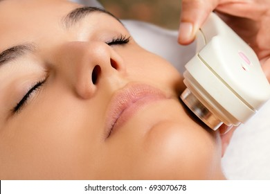 Macro close up portrait of woman having revitalizing ultrasonic skin tightening treatment in spa.