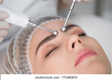Macro close up portrait of woman having cosmetic galvanic beauty treatment in spa.Therapist applying low frequency current with electrodes on face