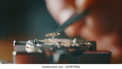 Macro close up of a professional watchmaker repairer working on a luxury mechanism watch gears engine in a workshop.