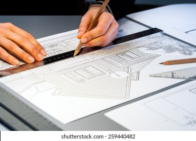 Macro close up of quantity surveyor working on architectural layout.