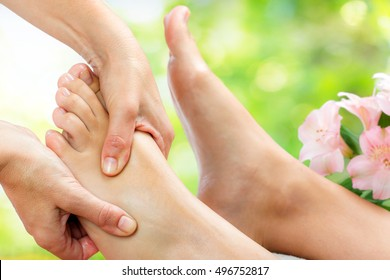 Macro close up of reflexologist doing massage on upper part of foot.Out of focus flowers in green background.