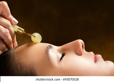 Macro close up side view of woman having beauty treatment in spa.Therapist applying jade roller on forehead.