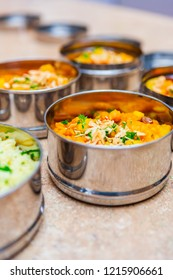 Macro Close Up of a Stainless Steel Tiffin (Dabba) Container with Curried Sweet Potato and Vegetable Stew with Rice and Almonds