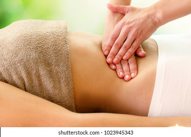 Macro close up of therapist applying pressure on stomach.Detail of hands massaging female belly.