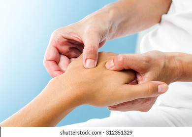 Macro close up of Therapist doing massage on female hand.Osteopath applying pressure on hand.