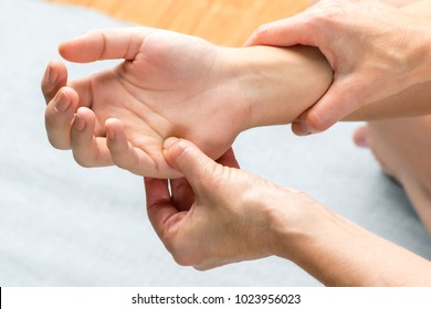 Macro close up top view of kinesiologist applying pressure on hand of female patient.