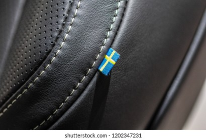 The macro close up view of Swedish flag on leather car seat.
