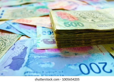 Macro close-up of 500 Argentine pesos banknotes stacked on bills of different value