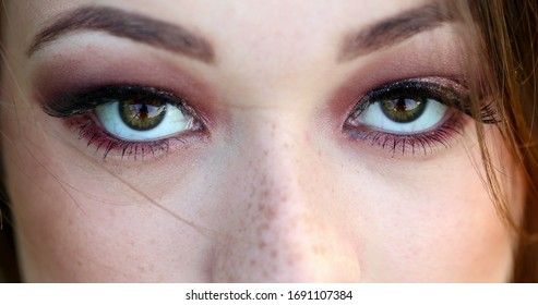 Macro closeup of beautiful girl opening and closing green eyes with eyelashes