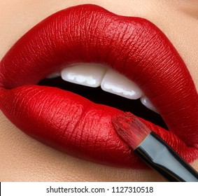 Macro and close-up creative make-up theme: beautiful female lips with red lipstick and brush