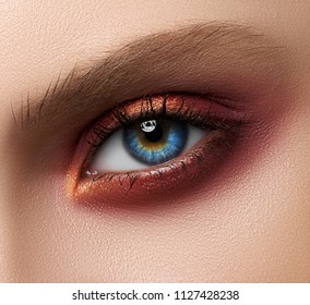 Macro and close-up creative make-up theme: beautiful female eyes with red shadows pigment