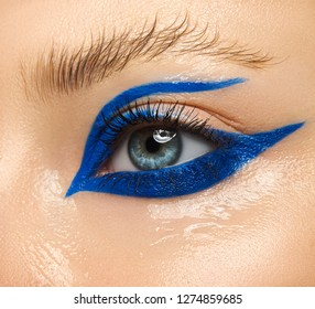 Macro and close-up creative make-up theme: Beautiful female eye with blue arrow pattern and wet skin