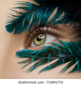 Macro and close-up creative make-up theme: beautiful female eyes with blue-green feathers