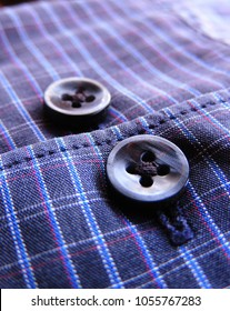 macro closeup of cuff of a vibrant navy blue checked formal shirt under sunlight with light blue & red stripes & dark blue buttons diagonally across the frame with cuff ends & stitching disecting both