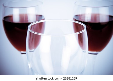 Macro close-up of empty glass in front of two glasses of wine, blue tint