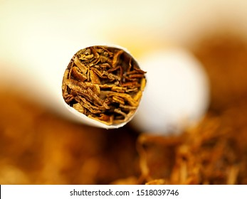 macro closeup of the front of a cigarette with a bed of fresh rolled tobacco and a yellow filter from another cigarette in the background