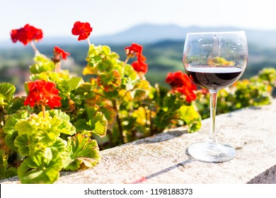Macro closeup of glass of red wine on balcony terrace by red geranium flowers outside in Italy with mountain view in Chiusi, Umbria or Tuscany