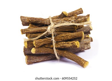 Macro closeup of a heap pile of Liquorice licorice roots sticks isolated on white