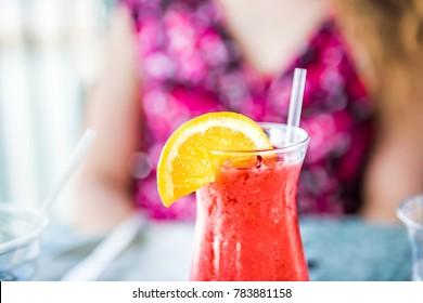 Macro closeup of iced strawberry daiquiri in glass on table
