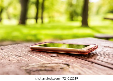 Macro closeup of lost generic light pink rose gold smartphone, phone left, forgotten in plastic clear case lying on table in outside summer park