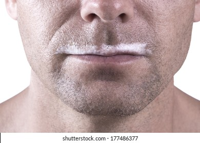 Macro closeup of lower half of man's face with thick white milk covering upper lip on white background