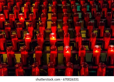 Macro closeup of many red candles with flame in church
